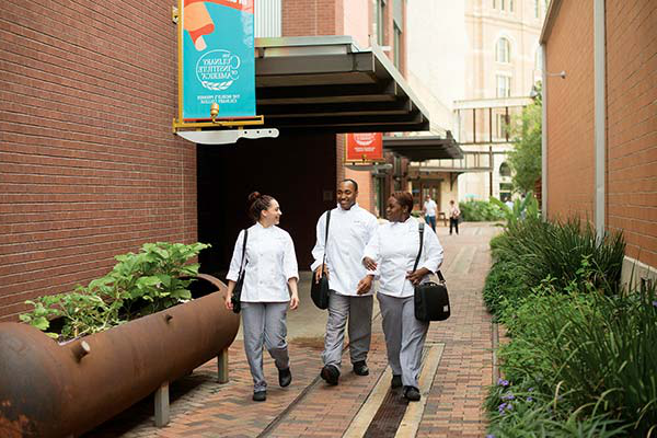 Students walking outside the 澳门人威尼斯app手机官网 in San Antonio, TX - a culinary school campus where students enjoy a spirited city life.